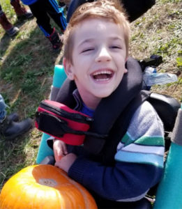 A boy is sitting in a specialized stroller with a neck harness and a pumpkin on his lap.