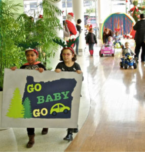 Two little girls walking in a mall holding a Go Baby Go Oregon followed by children driving switch adapted electric toy cars