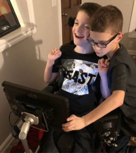 Twin boys, one in a wheelchair with a mounted communication device mounted, the other boy standing beside him touching the device.