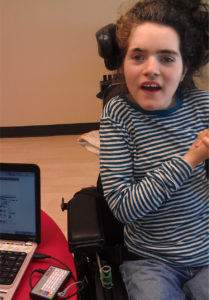 A young using the switches in a power wheelchair to scan through items on a laptop computer to make a selection.