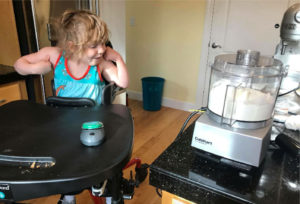 Little girl using a wireless switch to activate a food processor.