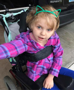 A little girl in a wheelchair wearing green cat ears on her head.