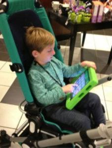 A little boy in a specialized stroller, activating buttons on an iPad for communication.