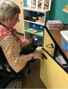 A woman in her wheelchair, opening a cupboard with handles adapted for easy-pull opening.