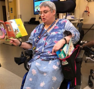A woman at work reading books to children, in her wheelchair with a book bag that was specially designed for her.