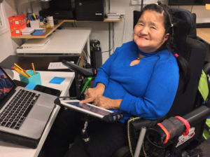 A woman is at work sitting in her wheel chair at work desk with a laptop computer, using here hand to activate an iPad communication device.
